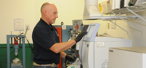 Technician operating a machine for cement testing.